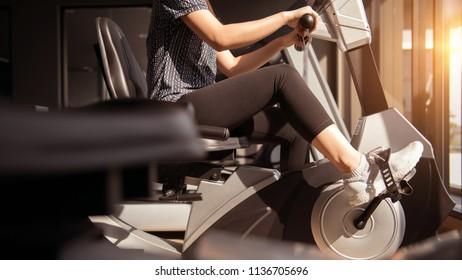 Young woman exercise bike cardio workout at fitness gym, Healthy lifestyle concept.