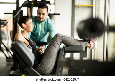 Young woman exercise in a gym with the help of her personal trainer