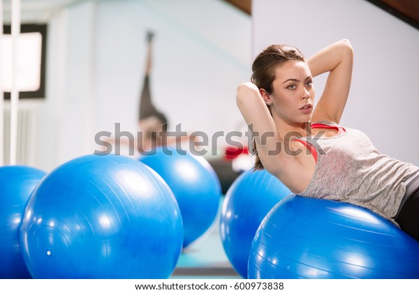 Young woman exercise with pilates balls in the gym