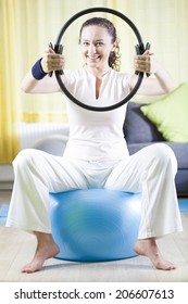 Young Woman Exercise With Pilates Ring, Pressing it With Hands