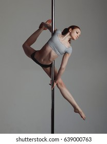 Young woman exercise pole dance gray background
