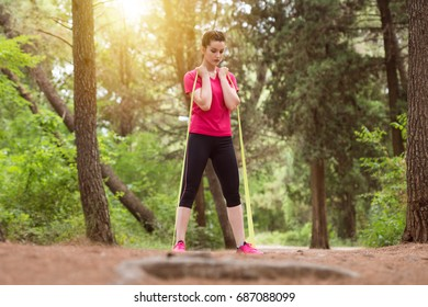 Young Woman Exercise with Resistance Band in Wooded Forest Area - Fitness Healthy Lifestyle Concept