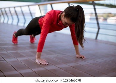 Young woman exercises on the promenade after running in the morning