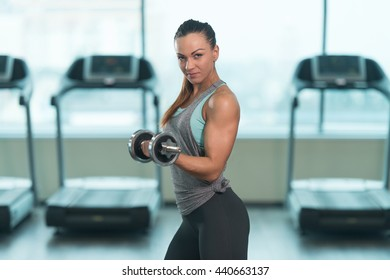 Young Woman Exercising Biceps With Dumbbells In The Gym And Flexing Muscles - Muscular Athletic Bodybuilder Fitness Model Doing Dumbbell Concentration Curls