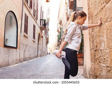 Young woman exercising in city street, leaning on stone wall stretching leg muscles, sport outdoors. Fitness working out healthy training. Teenager female healthy leisure recreation lifestyle.