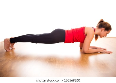 Young woman exercising - doing a plank in a studio