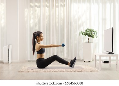 Young woman exercising with dumbbells in front of a tv at home