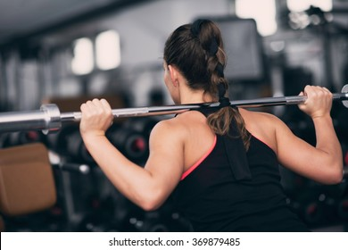 Young woman exercising in gym, doing squats with Olympic barbell