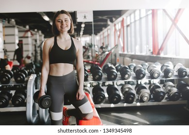 Young woman exercising in gym room. She pose on camer and smile. Resting after workout. Stand in gym room. Daylight.