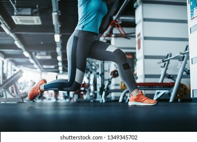 Young woman exercising in gym room. She does lunges in fitness room. Cut view. Sporty well-built woman exercising. Daylight in room.