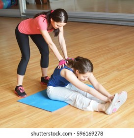 young woman exercising with her instructor
