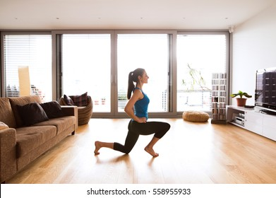 Young woman exercising at home, stretching legs.