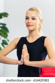Young woman exercising or meditating at home. Healthy lifestyle, training and individual sports concept.