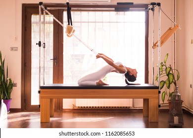 Young Woman Exercising on Pilates Reformer