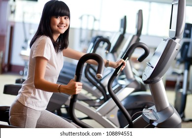 Young woman exercising on the xtrainer machines