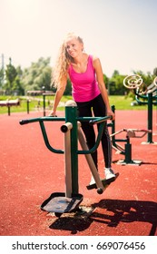 Young woman is exercising at outdoor gym.