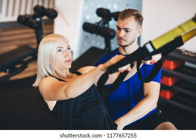 Young woman exercising with personal trainer at the gym. Healthy lifestyle and fitness.