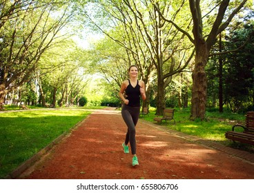 Young woman exercising running in a summer park