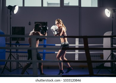 Young woman exercising with trainer at boxe and self defense lesson