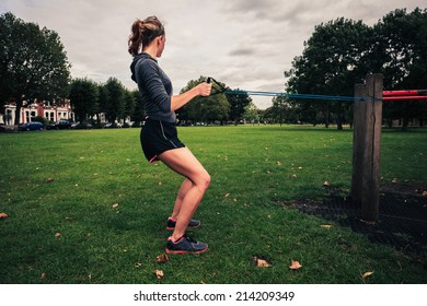 A young woman is exercising and working out with a resistance band in the park
