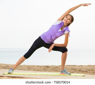 Young woman exercising yoga poses standing on sunny beach by ocean in morning