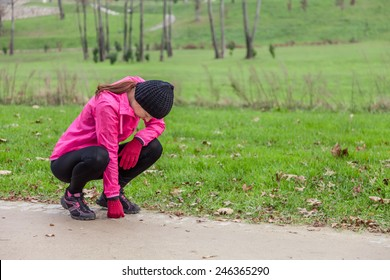 Young woman exhausted after running on a cold winter day in the track of an urban park.