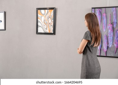 Young woman at exhibition in modern art gallery