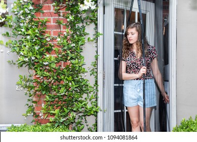 Young woman exiting house entering outdoor spring garden with hanging plant flowers covering brick wall in backyard porch of home by door, insect net