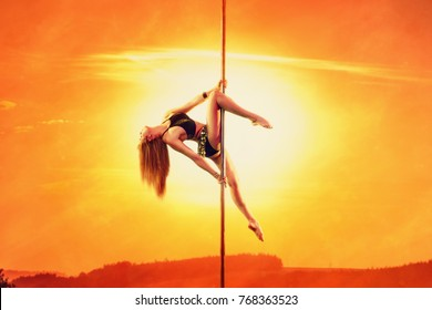Young woman exotic style pole dancing on sunset sky and sun warm red background. Asian style clothing.