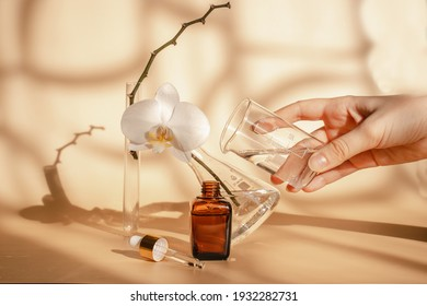 Young woman is experimenting with cosmetics. Essence for skin health on a beige  background. laboratory where cosmetics are created. Orchid extract. Exotic flowers. Unisex cosmetics for men and women