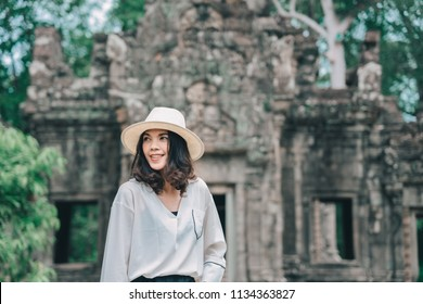 A young woman is exploring the ancient ruins of a buddhist temple city