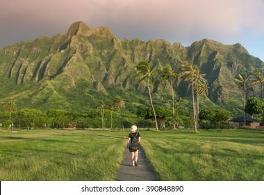 Young woman exploring Kualoa Regional Park under the Hawaiian mountains