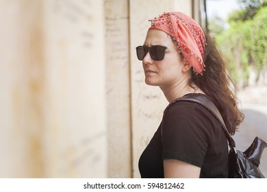 Young woman exploring old building with sunglasses and scarf