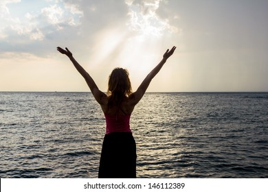 Young woman expressing freedom by the sea at sunset