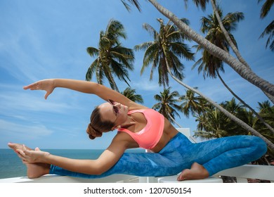 Young woman extends her back while and doing yoga in hotel terrace over sea view