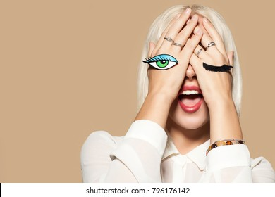 Young woman with eye and eyelashes painted on her hands. Studio portrait of fashionable model on beige background. Beautiful model with blonde hair. Concept of flirting and fun.