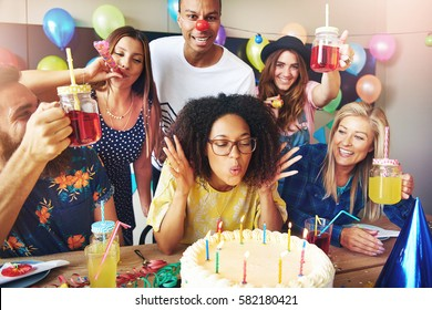 Young woman with eyeglasses blowing on cake candles while friends stand around her to celebrate a birthday or work anniversary
