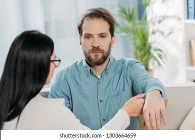 young woman in eyeglasses holding hand of bearded man during hypnotherapy