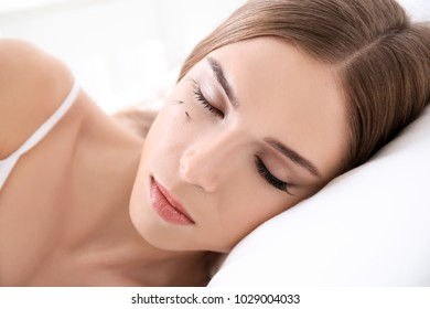 Young woman with eyelash loss problem sleeping in bed, closeup