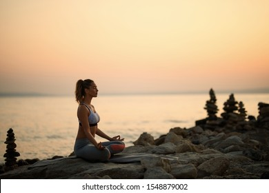 Young woman with eyes close practicing Yoga in lotus position on rocky beach at sunset. Copy space.