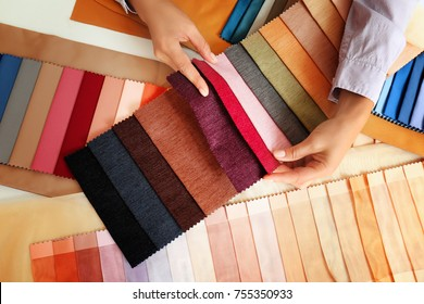 Young woman with fabric samples for curtains at table