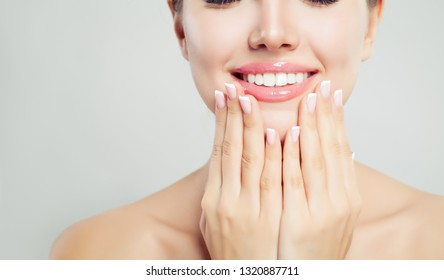 Young woman face closeup. Pink glossy female lips with natural makeup and french manicure hands