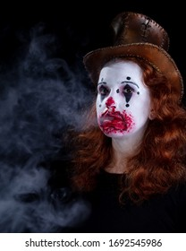 Young woman in face makeup as a tearful clown.