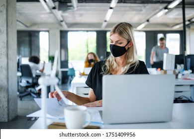 Young woman with face mask back at work in office after lockdown, working.