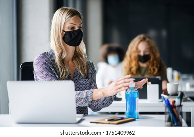 Young woman with face mask back at work in office after lockdown, disinfecting hands. - Shutterstock ID 1751409962