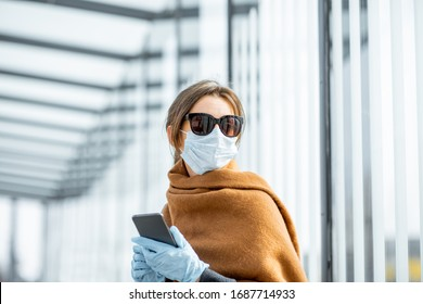 Young woman in face mask, medical gloves and sunglasses with a smart phone at the public transport stop during an epidemic. Concept of social distance and online communication