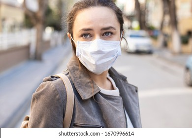 Young woman with face mask on the street. Novel Chinese Coronavirus self-protection concept