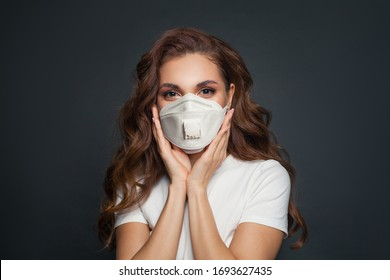 Young woman in face mask on dark gray background. Woman in medical mask portrait