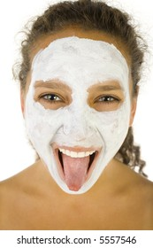 Young woman with face mask sticking her tongue. She's on white background. She's looking at camera.