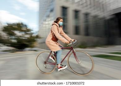 Joven cara máscara médica que conduce la carretera de bicicleta borrosa
